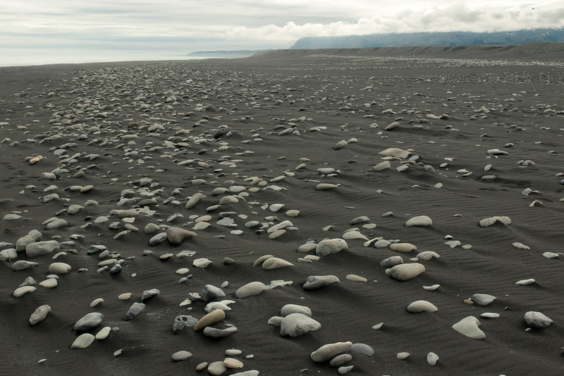 Breiðamerkursandur, a glacial outwash plain, composed of black sand and volcanic rock clasts - distal amongst the clouds to the slopes of the Vatnafjöll (mountains), the eastern flank of the cenral volcano, the Öræfajökull - Eastern region of Iceland.