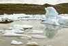 Weather sculpted iceberg shadows upon the placid glacial milk water of the Fjallssárlón (Mountain Lagoon).