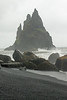 Reynisdrangar (pillars) or sea stacks - North Atlantic waves - volcanic rock talus boulders, sea-eroded clasts and black sand along the Reynisfjara (beach).