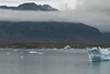 Jökulsárlón (Glacier Lake Lagoon) with glacial ice afloat - beyond amongst  the cloud bank is the volcanic rock slopes of the Fellsfjall (mountain) - with distal the snow patches upon the Þverárfjall (mountain).