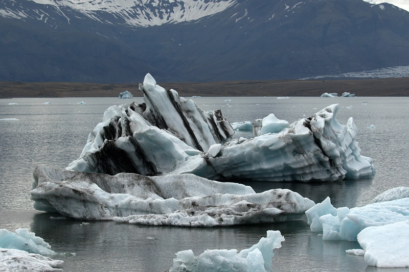Glacial icebergs, bergy bits, and growlers upon the Jökulsárlón (Glacier River Lagoon) - beyond the glacial till moraine, to the southern edge of the Breiðamerkurjökull (glacier), adjacent the Breiðamerkurfjall (mountain).