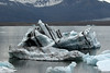 Glacial icebergs, bergy bits, and growlers upon the Jökulsárlón (Glacier River Lagoon) - beyond the glacial till moraine, to the southern edge of the Breiðamerkurjökull (glacier), adjacent the Breiðamerkurfjall (mountain).