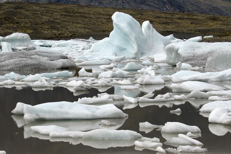 Glacial ice afloat the turbid glacial flour water of the Fjallssárlón (Mountain Lagoon).