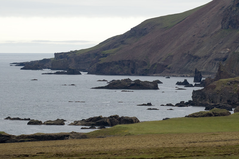 Volcanic rock islets and a sea stack upon the Vopnafjörður (fjord), along the shoreline below the steep slope and volcanic rock sea cliffs of the Búr Mountain.