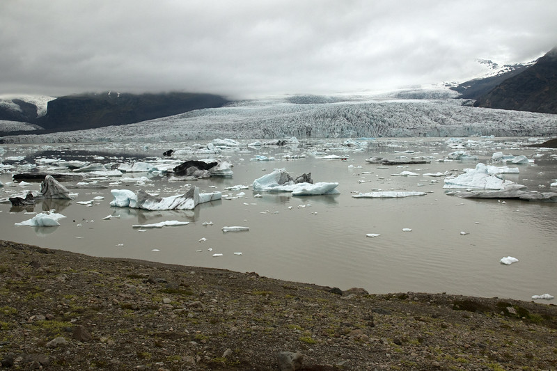 From the glacial till terminal moraine slope - down to the  Fjallssárlón (Mountain Lagoon), with icebergs, bergy bits, and growlers afloat the glacial flour water - with beyond (l to r) and amongst the clouds, the Hrútárjökull (glacier), Ærfjall (mountain), Fjallsjökull (glacier), Breiðamerkurfjall (mountain) - Vatnajökull National Park - Eastern region of Iceland.