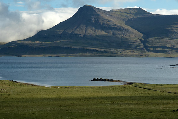 From Skaflavíkurtangi (point), along the grassland slope - across the Breiðdalsfjörður (Wide Valley Fjord), to (l) the Gunnhildarey (island) - with above the Goðaborg and its steep streaming northern slope, then up the ridge and Stuttidalur (valley) to the Sátur, peaking at around 2,250 ft. (716 m) - Eastern region of Ieland.
