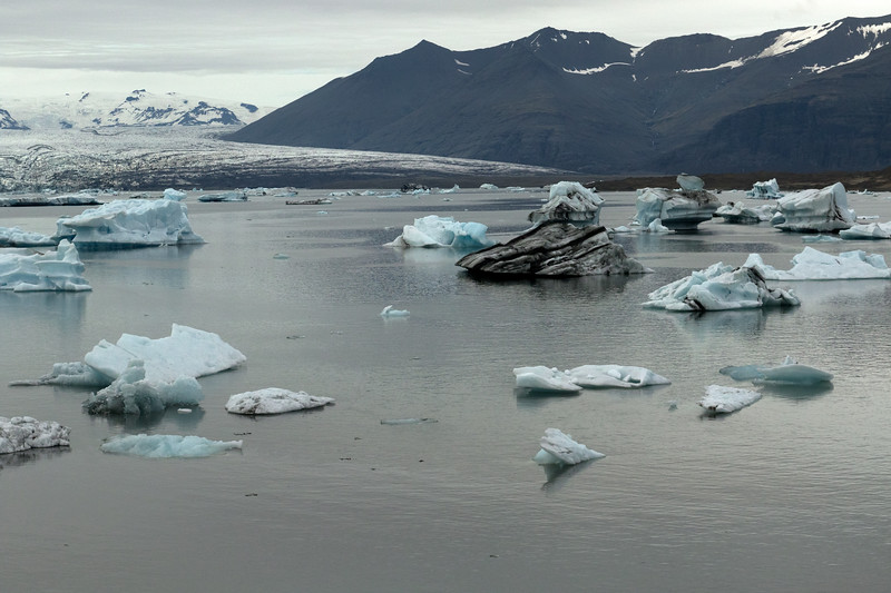 Icebergs, bergy bits, and growlers adrift the brackish water of the Jökulsárlón (lagoon) - beyond to the calving glacier of the Breiðamerkurjökull - adjacent the slopes of the Veðhurárdalsegg (ridge) , Fremri-Veðhurárdalur (front valley), and Hellrafjall (mountain) - with distal the Esjufjöll (mountains), mostly covered with snow and ice - located in the Vatnajökull National Park - Eastern region of Iceland.