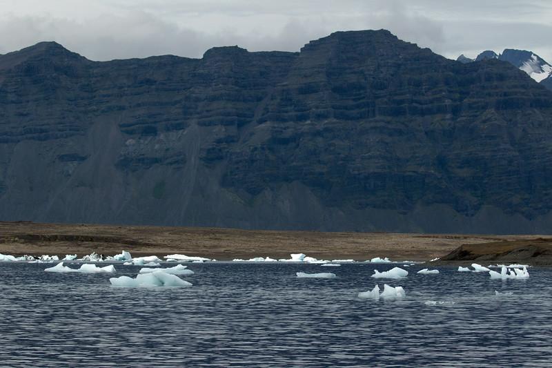 Calved glacial ice afloat the Jökulsárlón (Glacier River Lagoon) - glacial till moraines - Fellsfjall (mountain) - and distal the peak of Þverártindur.