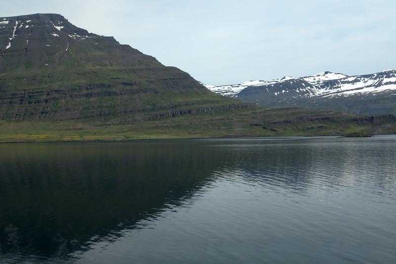 Across the placid water of the Reyðarfjörður (fjord) - to the Stórhólmi (island) - with beyond a few snow patches  upon the Holmatindur (peak) - and distal to the Ófeifsfjall (mountain) and distal the Hólafjall (mountain).
