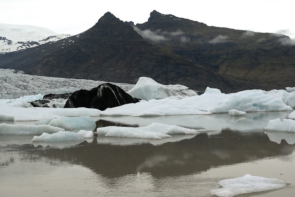 Reflections upon the Fjallssárlón (lagoon) - of the glacial till cloaked iceberg, calved from the Fjallsjökull (glacier), and the Breiðamerkurfjall (mountain), with its Miðaftanstindur (peak) rising to about 2025 ft. (618 m), and beyond the clouds the Rákartindur (peak) rising up to about 2,540 ft. (774 m).