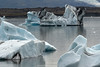 Icebergs afloat the Jökulsárlón (lagoon) -  beyond the glacial till moraine  - to the edge of the Hrútárjökull (glacier) flowing adjacent the Múli (mountain).