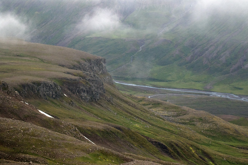 Along the volcanic rock slope, ledges, and a snow patches along the western Seldalsfjall (mountain) - below to the Dalsá (river) - then up the slope of the Vindfellsfjall (mountain), amongst the heathland vegetation, flowing stream, and clouds - Eastern region of Iceland.