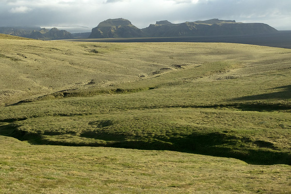 Across the Hjorleifshraun (lava field), the central slopes of the Hjörleifshöfði (headland), clustered with moss, lichen, herb, grass, and heathland vegetation - to the Hafursey, Skalafrfjall, and Kistufell (mountains) - with adjacent the southeastern slopes of the Katla Volcano and Mýrdalsjökull (ice cap).