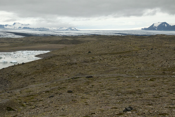 Across the terminal moraine slope, composed of volcanic rock now cloaked with moss, herb, heath, and willow vegetation - beyond the far eastern area of the Fjallssárlón (Mountain Lagoon), with the calved glacial ice afloat - to the Breiðamerkurjökull (glacier), flowing amongst the nunatak (glacial rock islands) known as the Esjufjöll (mountains) and the Veðhurárdalsfjöll (mountains) - Vatnajökull National Park - Eastern region of Iceland.