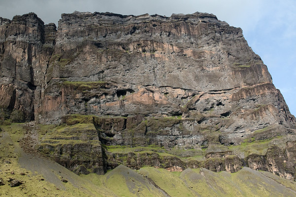 Patch of sunlight upon the southern end of mount Lómagnúpur (peak), a sea cliff composed of volcanic palagonite rock - located at the eastern boundary of the Katla UNESCO Global Geopark - Southern region of Iceland.