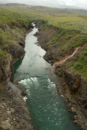 Jökulsá Brú (river) - here with its glacial water flowing between the headlands of the Jökulsárshlíd and Hróarstunga - and adjacent the foss (waterfall) flowing from a lækur (stream) - Eastern region of Iceland.