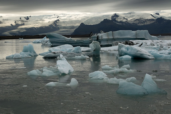 """Jökulsárlón (Glacier River Lagoon) - here amongst the icebergs, bergy bits, and growlers at the source of the Jökulsá (river), which is connected to the sea via a narrow and deep channel that measures about .3 mi. (.5 km) long, thus this lake fluctuates with Iceland's semidiurnal tides - this image nearing max flood tide, the day after """"Full Moon"""" or """"Syzygy"""", creating a greater tidal effect, yet it is nearing the """"Aphelion"""" (when the earth is at its farthest orbital point, creating less tidal effect) - the tidal rise today is about 2 ft. (.6 m) - with distal the Múli (mountain), Hrútárjökull (glacier), Ærfjall (mountain), Fjallsjökull (glacier), and Breiðamerkurfjall (mountain)."""