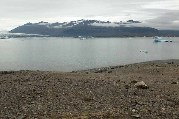 From atop the terminal moraine of glacial till - down to the Jökulsárlón (lagoon), with glacial ice afloat from the calving glacier of the Breiðamerkurjökull - adjacent the Veðhurárdalsegg (ridge), Hellrafjall and Fellsfjall, (mountains), with the Midfellstindur (peak) rising up to about 3,645 ft. (1,111 m).