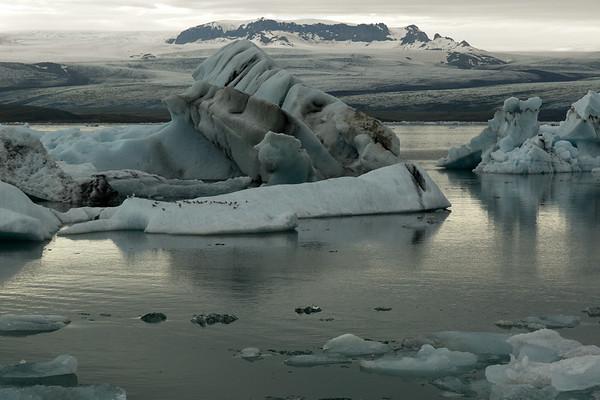 Glacial ice afloat the Jökulsárlón (lagoon) - beyond the ice stream of the Breiðamerkurjökull (glacier), surrounding the Fjölsvinnsfjöll (mountains).