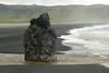Arnardrangur (Eagle Rock), a volcanic basalt rock sea stack - adjacent the water from the Dyrhólaós estuary, flowing into the Atlantic Ocean along the black sand beach of Reynisfjara - distal the edge of the estuary and the slope of the Reynisfjall (mountain).
