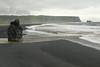 Arnardrangur (Eagle Rock) sea stack - adjacent the water from the Dyrhólaós estuary, flowing into the North Atlantic - beyond to the distal sea stacks of Reynisdrangar.