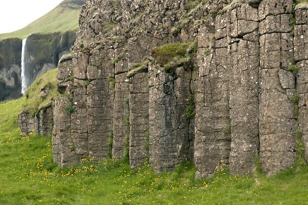 Dverghamrar (Dwarf Rocks), comprised of jointed columnar basalt rock prisms - distal the Siðufoss (falls), adjacent a smaller waterfall cresting the ledge.