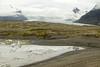 Glacial bergy bits and growlers afloat the Fjallssárlón (Mountain Lagoon) - glacial till moraine forming the eastern peninsula of the glacial lake - beyond the Fjallsjökull (Mountain Glacier) streaming between the Ærfjall and Breiðamerkurfjall (mountains) - Vatnajökull National Park.