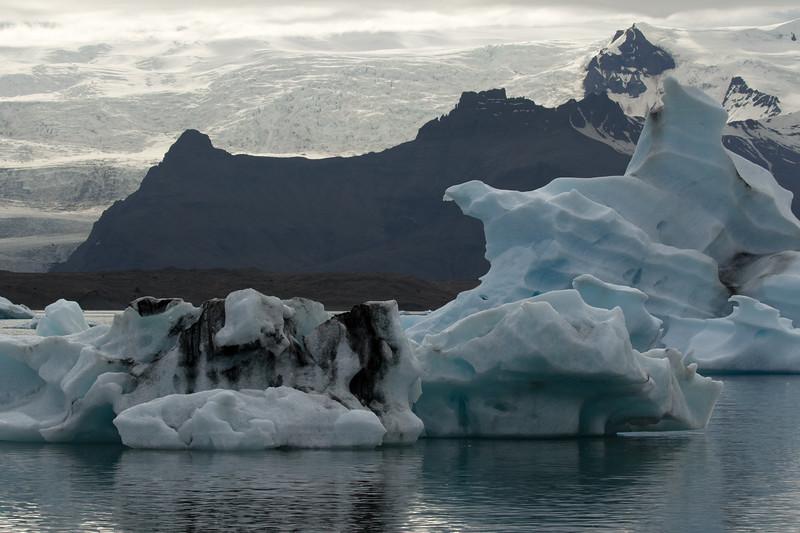 Glacial till upon the icebergs afloat the Jökulsárlón (Glacial River Lagoon) - beyond the terminal moraine to the igneous rock slopes along the Breiðamerkurfjall (mountain), with above the Antafjallstindur (peak) - adjacent the Fjallsjökull (Mountain Glacier).