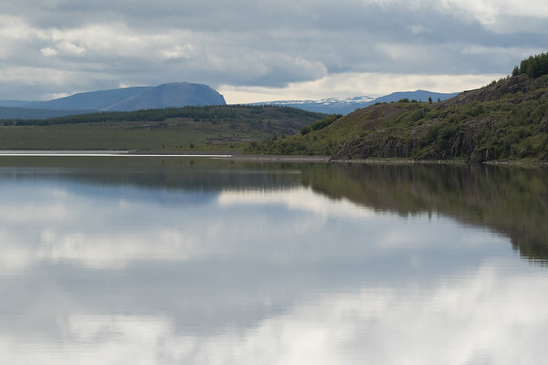 Rippleless reflection upon the glacial water of Lake Lögurinn, the northern area - from the Stekkjarklettar (cliffs) - across to the timberline along the Þhósneshöfði (head) - then directly beyond the tip of the headland at Röðlar, rising to about 1,667 ft. (508 m) - with distal the slopes, ridges, peaks, and snow banks along the southern highlands of the East Fjords of Iceland.