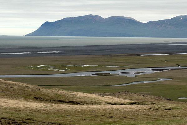 From the lower slope of the Ketilsstaðafjall (mountain) - down to and across the Jökulsá Brú (river), to the headland of Hróarstunga, then the Lagarfljót (river) - with beyond the volcanic rock alluvium along the Nýjagras coastline, adjacent the shoreline of the Héraðsflói (bay) - with distal the Ösfjöll (mountain), which forms the southeasternmost boundary of the bay, peaking at around 2,287 ft. (697 m), along the along the Grjótfjall (mountain), - which is just north of the northernmost area of the East Fjords of Iceland.