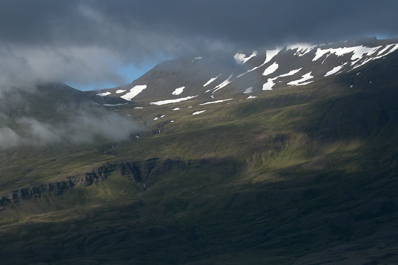Beyond the clouds to the sunlight patch upon the snow banks and cascading waterfalls upon the eastern slopes and ridges along the Berufjörður (fjord).