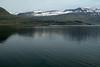 Across the placid water of the Reyðarfjörður (fjord) - to the Stórhólmi, Flathólmi, Ysthólmi, Hraukhólmi, and Handhólmi (islands) - adjacent the Hólmanes (peninsula) and lower eastern slope of the Holmatindur (peak) - with distal (l to r) are the Hólafjall, Ófeifsfjall, and Svartafjall (mountains).