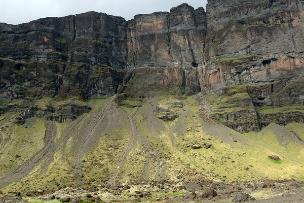 Steep craggy cliff face and jagged ridge top - with slopes clustered mostly with lithophytic moss, amongst the volcanic rock scree and talus - along mount Lómagnúpur (peak) - Southern region of Iceland.