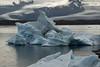 Icebergs upon the Jökulsárlón (lagoon) - beyond the glacial till terminal moraine - to the Múli (mountain), Hrútárjökull (glacier), Ærfjall (mountain), and the Fjallsjökull (Mountain Glacier) - Vatnajökull National Park - Eastern region of Iceland.