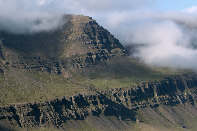 Craggy igneous rock slopes and ridges of the Dýjatindur, amongst the clouds.