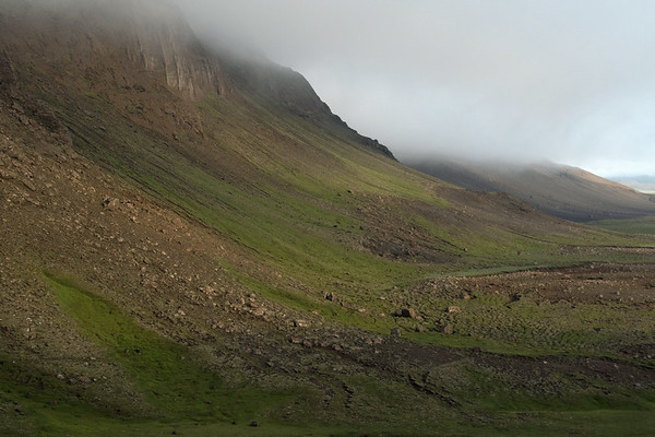 Fallen talus boulders along the slope of the Fjallagarður (Mountain Dike), with its ridge amongst the clouds - Northeastern region of Iceland.