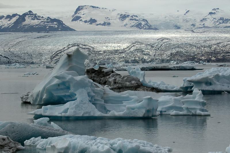 Jökulsárlón (lagoon), displaying the glacial ice afloat, which has calved from the Breiðamerkurjökull (glacier) - with distal the Esjufjöll (mountains).