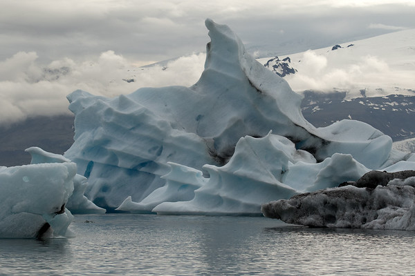 Jökulsárlón (Glacier River Lagoon) with weather sculpted icebergs afloat - beyond is a glimpse of the Hrútárjökull (glacier), adjacent the volcanic rock slopes of the Múli (mountain), with above amoungst the clouds is the Rótarfjallshnúkur (peak), rising to around 3,366 ft, (1,026 m).