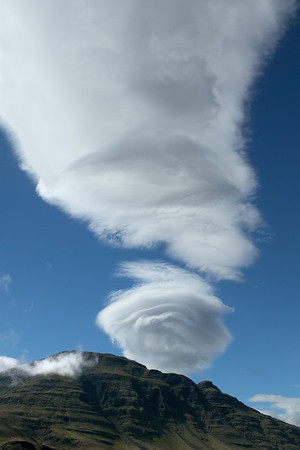 Altocumulus Lenticular - a lens-shaped cloud that normally forms when stable, warm, and moist air moves up a mountain side, subsequently being pushed over the top to the opposite sidewhere it then drops, cools, and creates layered condensation on the dowwind side of the mountain - this cloud situated above the moss cloaked slope and ridge along the southern area of the Melrakkanes (peninsula) - the upper northern ridge along the Álftafjörður (fjord) - Eastern region of Iceland.