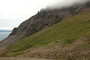 Across the volcanic talus rock slope and heathland vegetation, to the  craggy ridge along the cloud banks below the Heiðarhnjukúr (peak) - down to the Vopnafjörður (fjord).