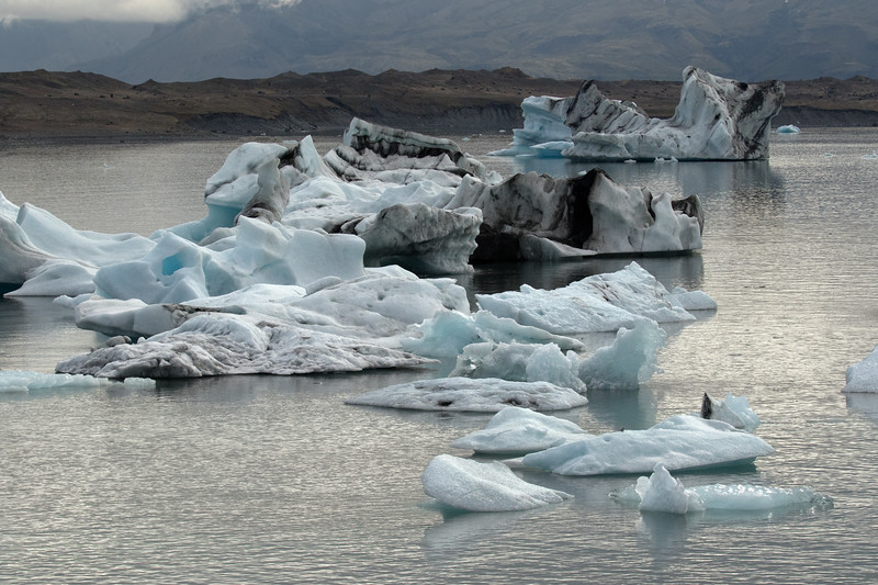 Jökulsárlón (Glacial River Lagoon) - with icebergs and bergy bits afloat - beyond the terminal moraine to the distal slopes of the Múli (mountain).