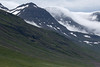 Vegetated slopes, jagged ridges, scattereed snow banks and clouds amongst the Hólafjall (mountain) - Eastern region of Iceland.