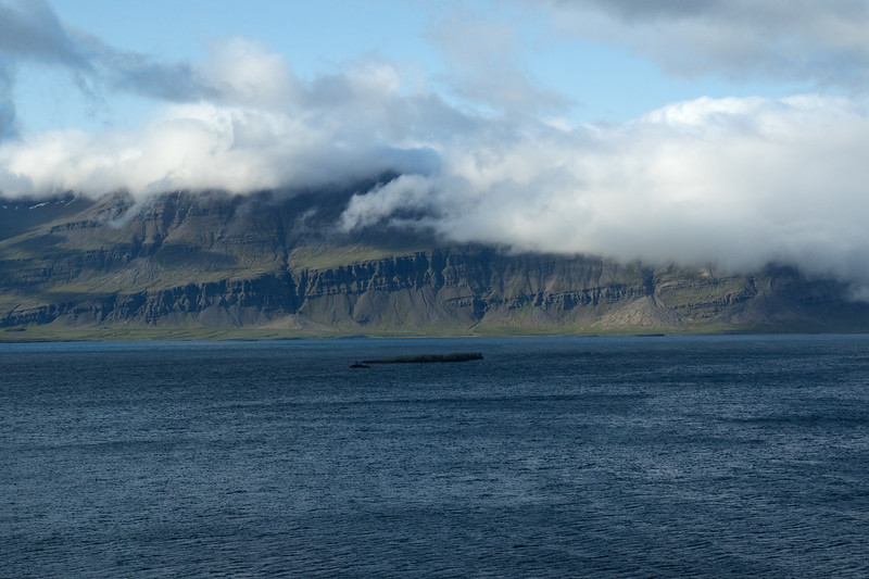 Across the  Breiðdalsfjörður (Wide Valley Fjord) and Spaðhólmi (island) - to the cloud bank above the Merkidalur (valley) and Ófærugil (gorge), both with volcanic rock forming a triangular alluvial fan at their mouths.