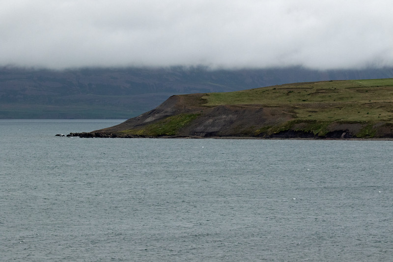 Across the Arnarnesvík (bay) displaying a few white caps, along the western area of the Eyjafjörður (fjord) - to the northern end and shoreline of the Galmaströnd (coastal plain) - with distal below the cloud bank to the slope of the Kræðufell (mountain) - Northeastern region of Iceland.