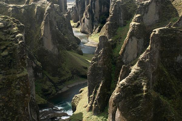 Down the Fjaðrárgljúfur (Feather River Gorge), displaying its craggy volcanic rock slopes clustered with lithophytic vegetation - along the meandering Fjaðrá (river) - distal is the Skaftá (river).