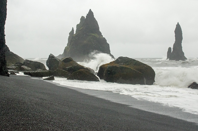 Waves breaking upon the Reynisdrangar (pillars) or sea stacks, rising about 200 ft. (60 m) above the North Atlantic Ocean - Southern region of Iceland.