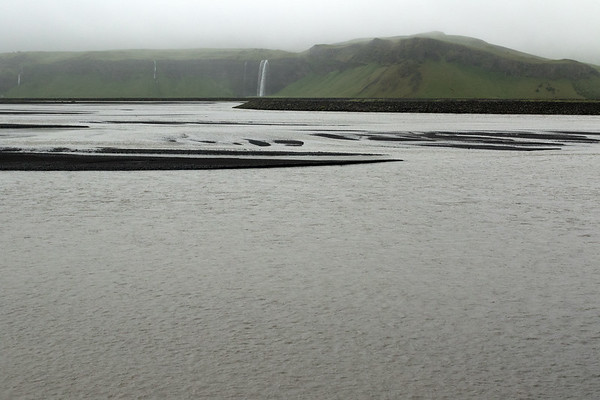 Katla Geopark, established in 2011 - here at its westernmost boundary, the Markarfljót (river) - beyond eastward is the Seljalandsfoss (falls), with the water from the Seljalandsá (river) plunging about 200 ft. (60 m) from the western end of the Eyjafjöll (Island Mountain) Volcano, which is also called Eyjafjallajökull (which includes the ice cap or glacier atop this volcano) - with (l) the Gljúfrafoss (falls) also know as the Gljúfrabui (Canyon Dweller) - Southern region of Iceland.