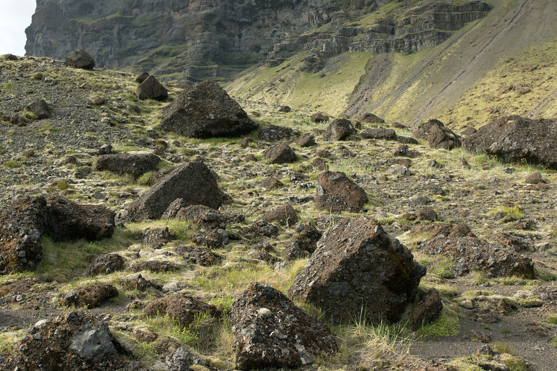 Fallen talus boulders of volcanic rock, pillow basalts fused with palagonite - along the base of mount Lómagnúpur (peak).