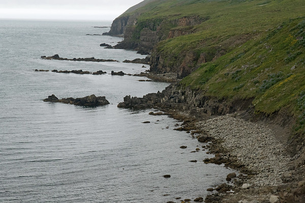 Fallen volcanic rock boulders and steep sea cliffs along the shoreline of the Ólafsfjörður (fjord) - along the lower slope of the Kristufjall (mountain) - Northeastern region of Iceland.