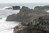 Dyrhólaey, volcanic basalt rock promontory - out to the North Atlantic wave crashing into the skerries (rocky islets).